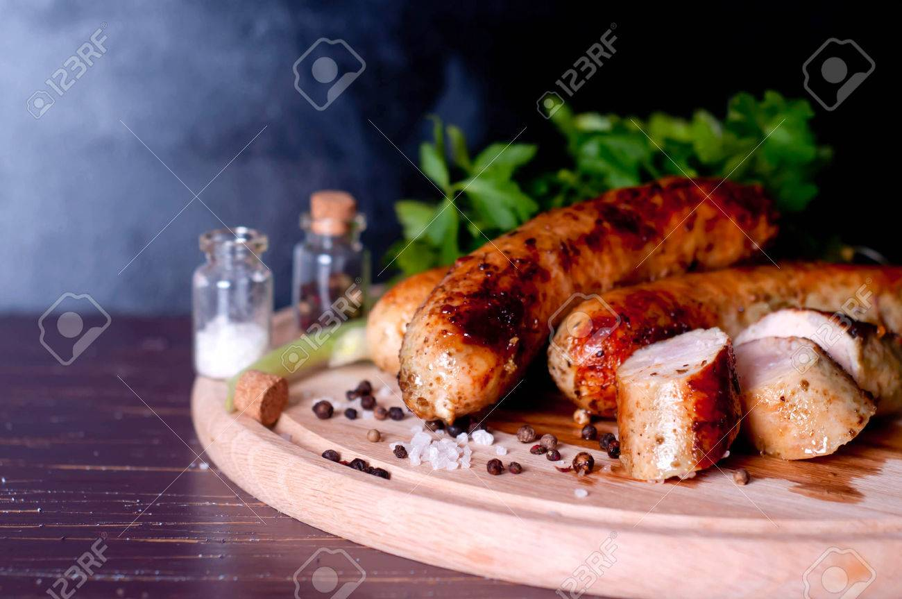 Barbecue tongs with sausege in dark background - 36570897