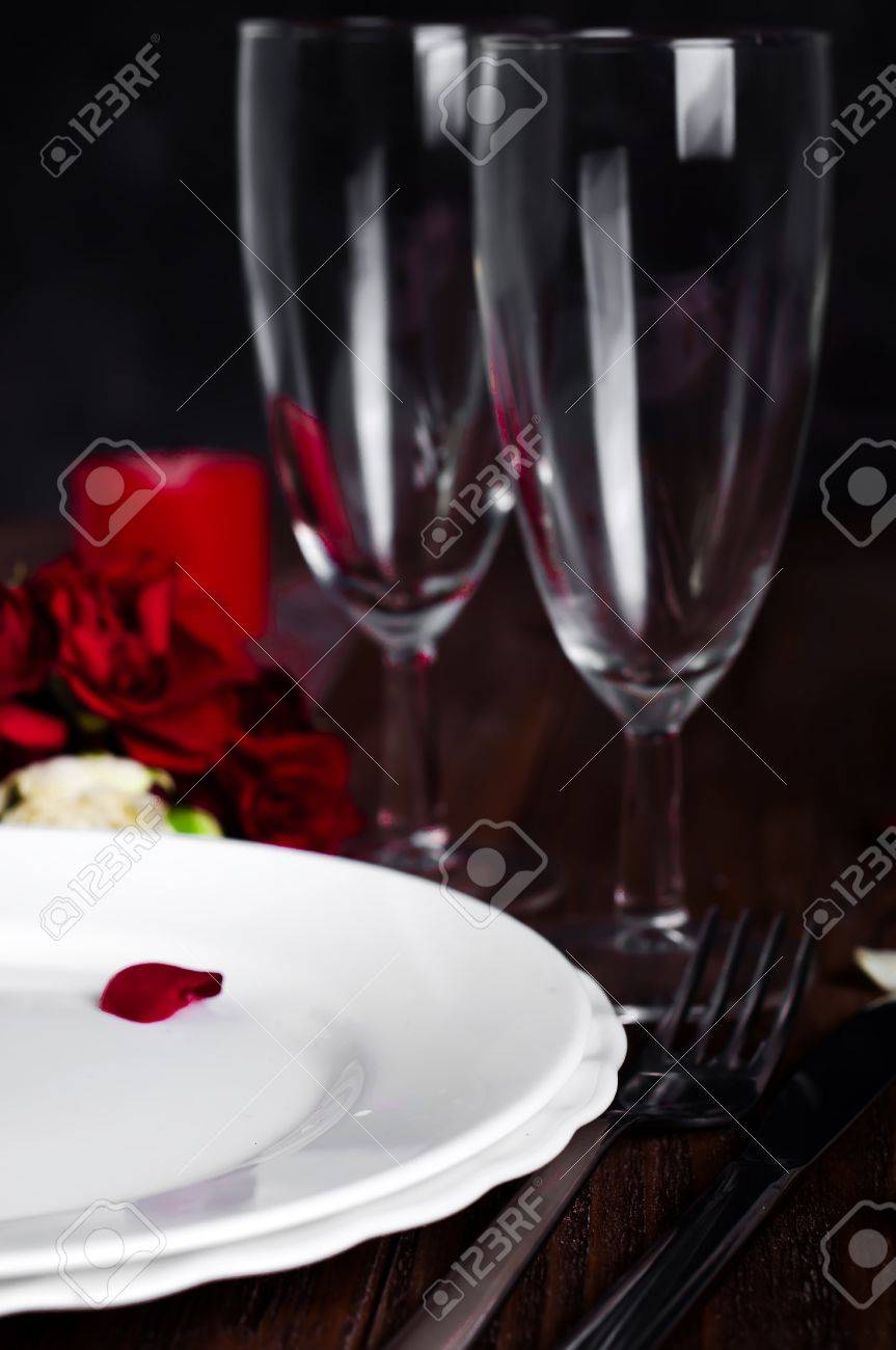 Romantic Valentine Candle Light Dinner Table Setting with red roses gift and burning candles against & Romantic Valentine Candle Light Dinner Table Setting With Red ...