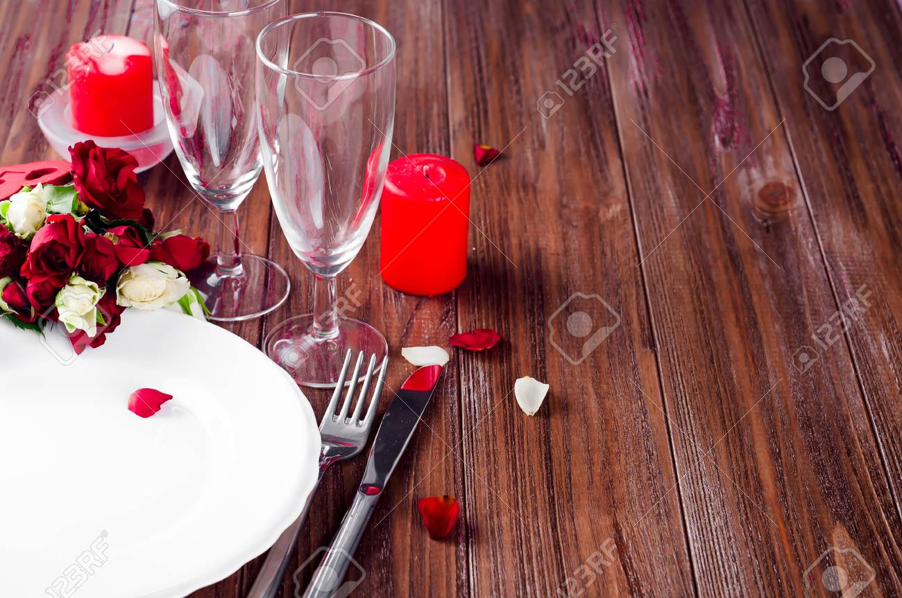 Romantic Table Setting With Roses Plates And Cutlery On A Darl