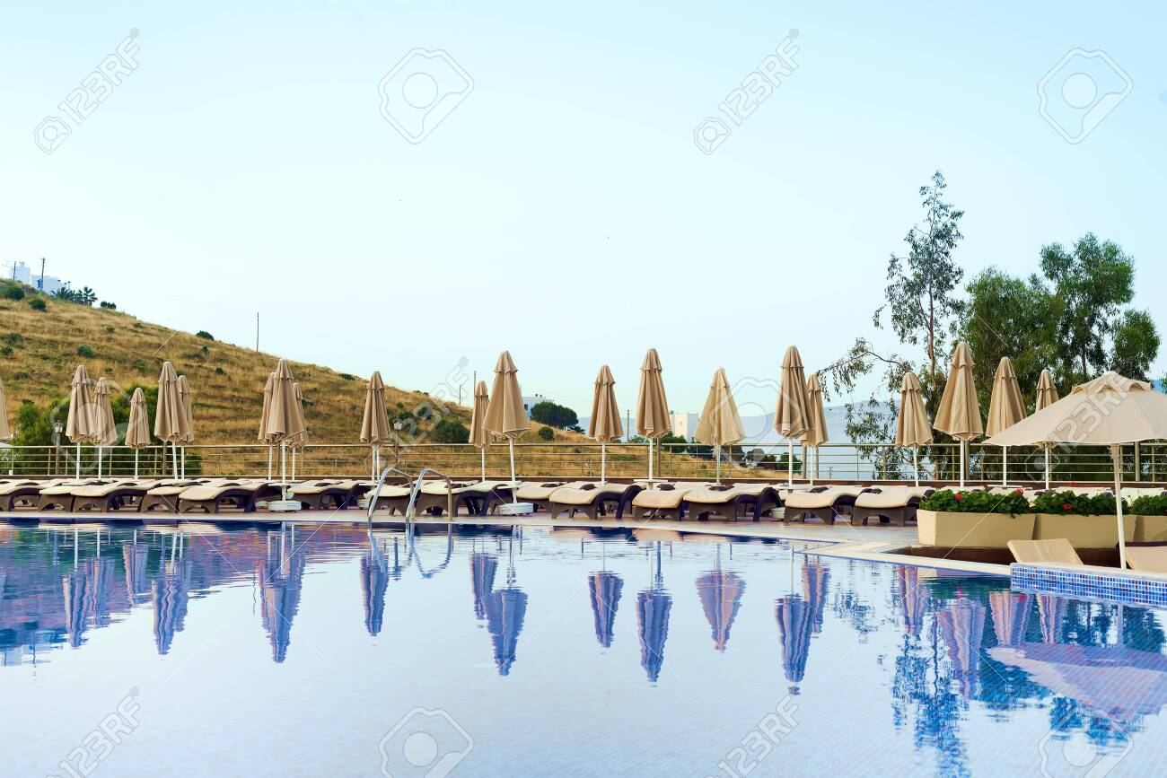 Outdoor luxury swimming pool, umbrellas, sun beds with reflection..