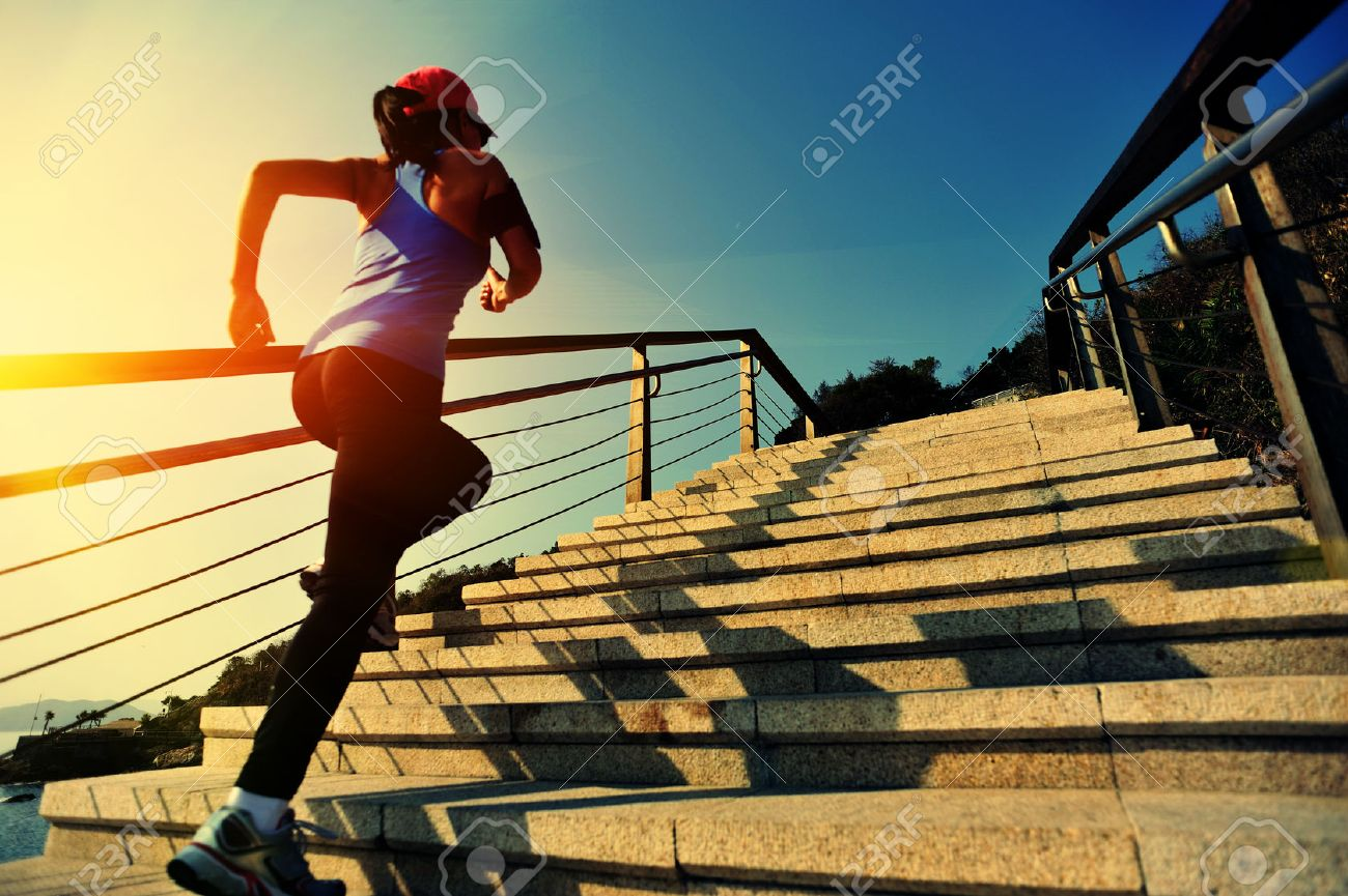healthy lifestyle sports woman running up on stone stairs sunrise seaside - 49993472