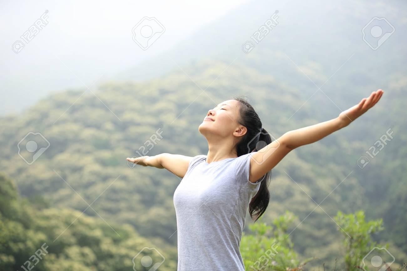 cheering woman enjoy the beautiful view at mountain peak - 49993477