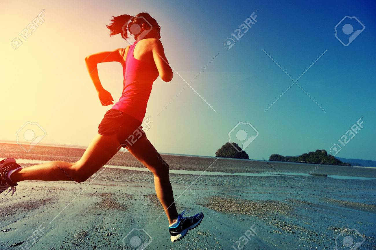 young healthy lifestyle woman running at sunrise beach - 50007183