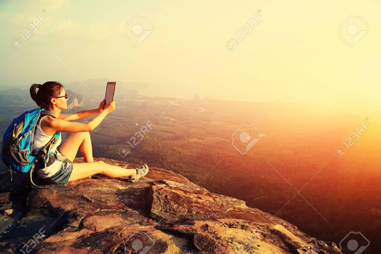 woman hiker use digital tablet at mountain peak Stock Photo - 50013044