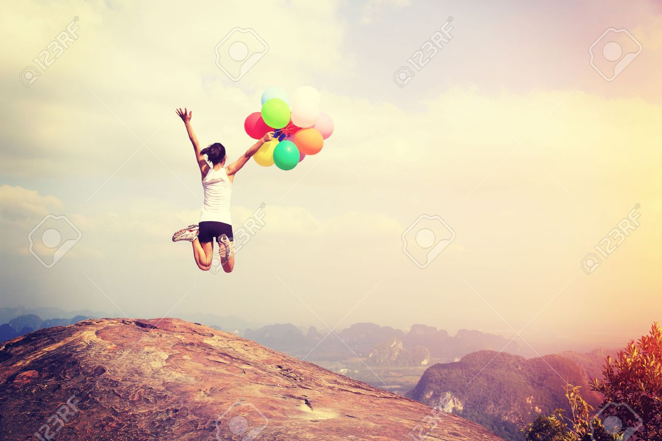 cheering young asian woman jumping on mountain peak rock with colored balloons - 50002429