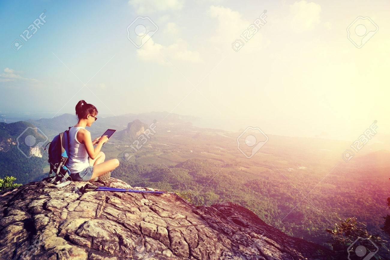 woman hiker use digital tablet at mountain peak - 50006725