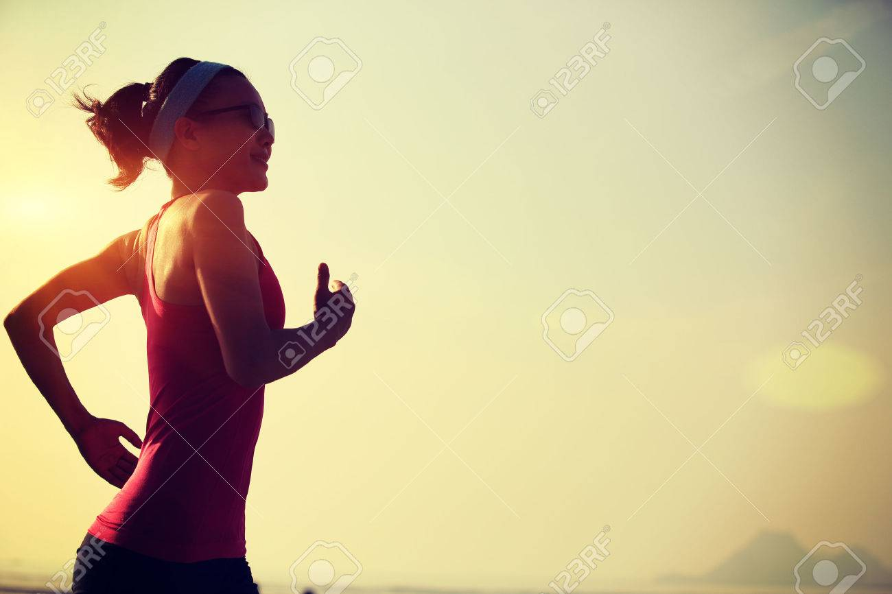 young healthy lifestyle woman running at sunrise beach - 50011950