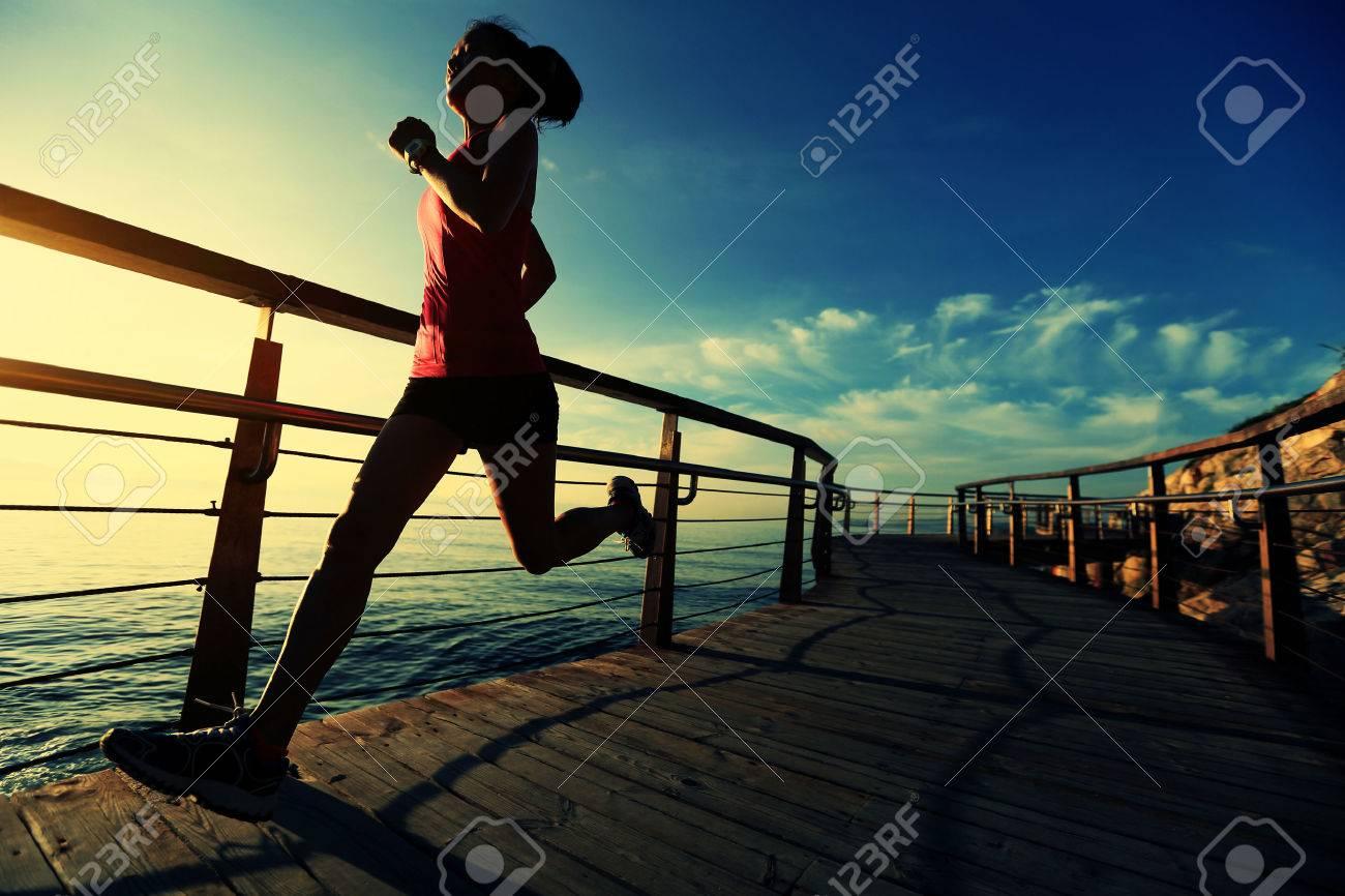 healthy lifestyle sports woman running on wooden boardwalk sunrise seaside - 50148788