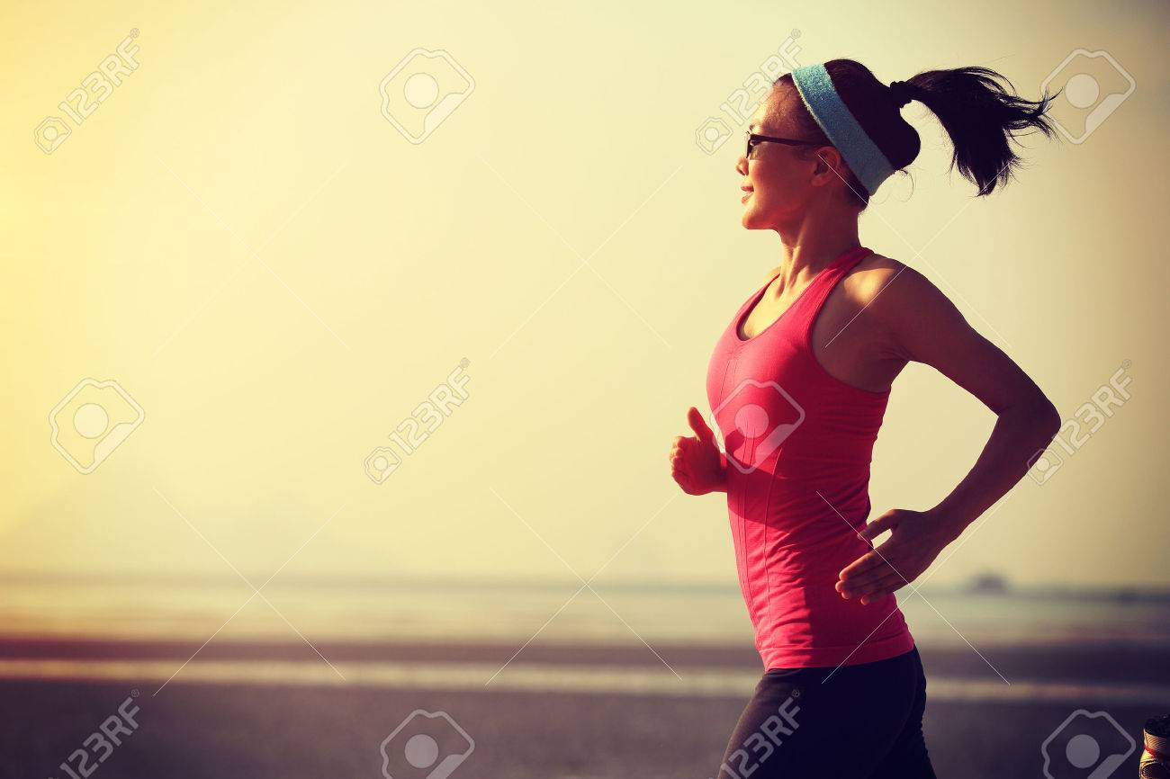 young healthy lifestyle woman running at sunrise beach - 50194604