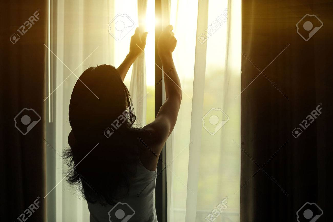 young woman opening curtains in a bedroom - 50155749
