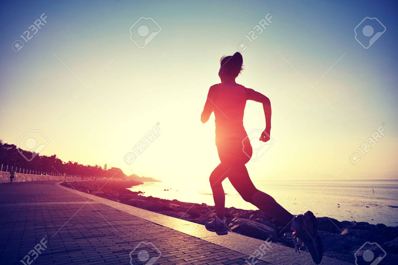 Runner athlete running at seaside. woman fitness silhouette sunrise jogging workout wellness concept. - 50194312