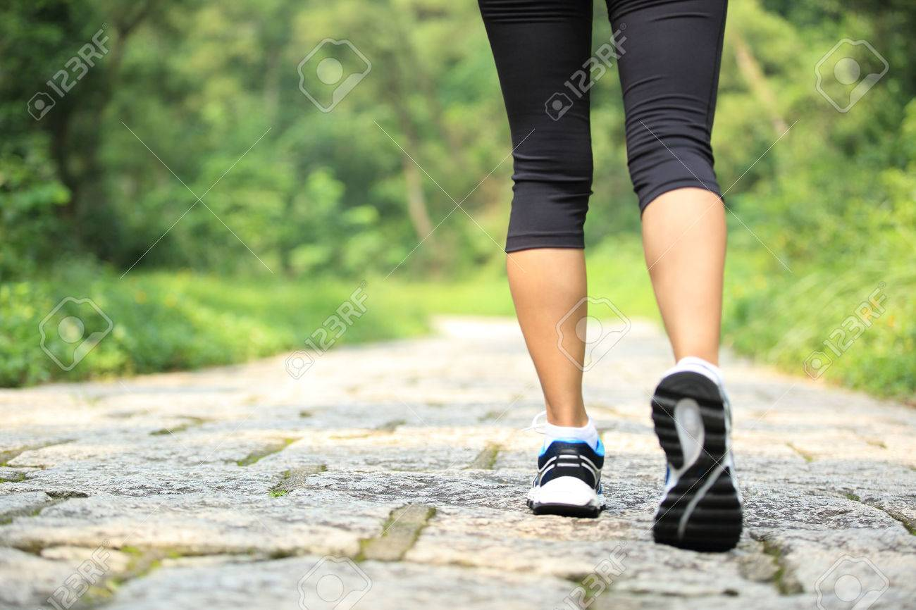 young fitness woman walking at forest trail - 50429401