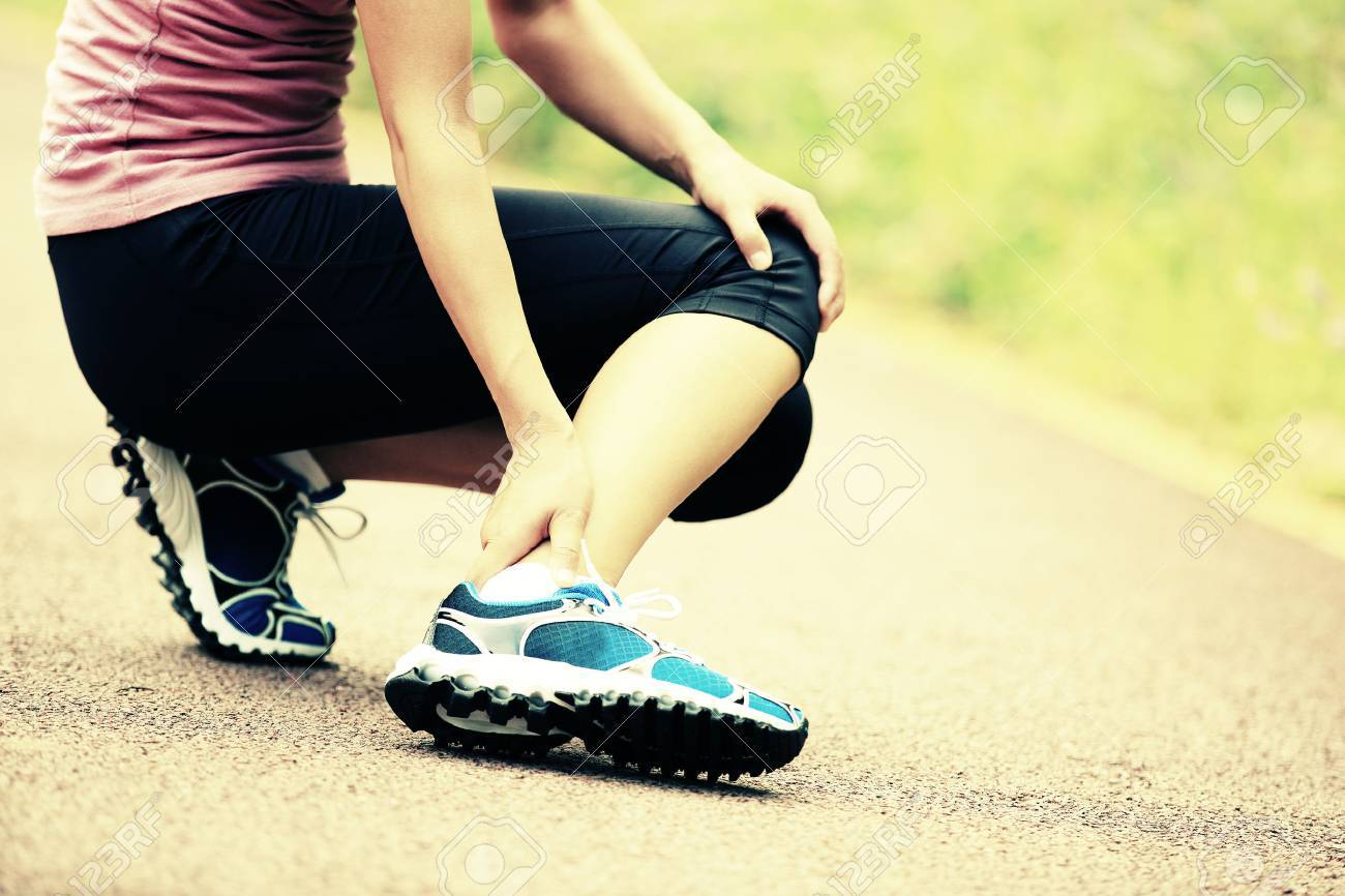 woman runner hold her twisted ankle - 50555885