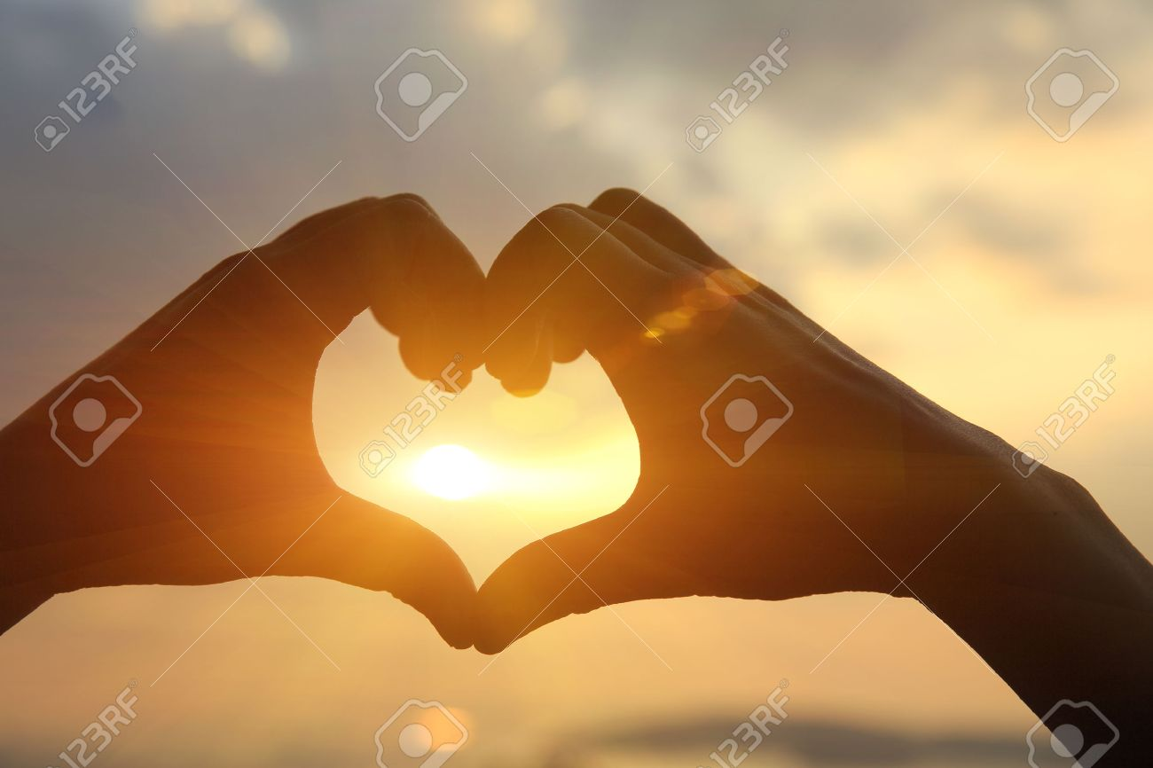 Heart shape making of hands against bright sea sunset and sunny golden way at water - 50402904