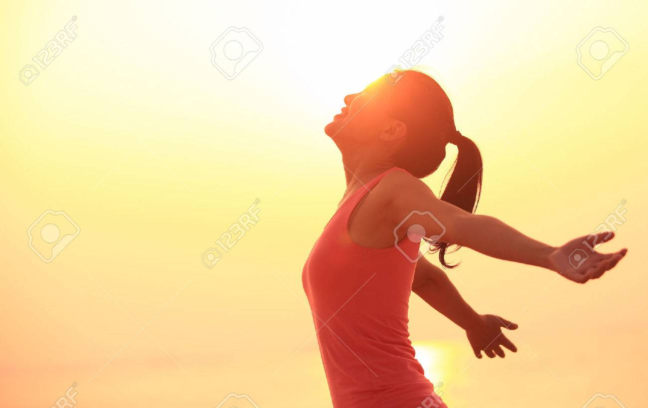 young fitness woman open arms under the sunrise at sea - 51163649