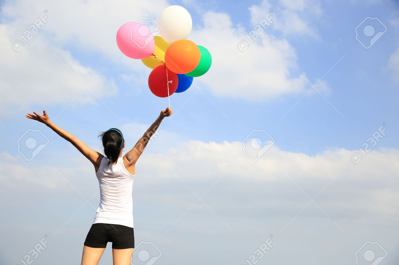young woman cheering on mountain peak with colorful balloons - 51394096