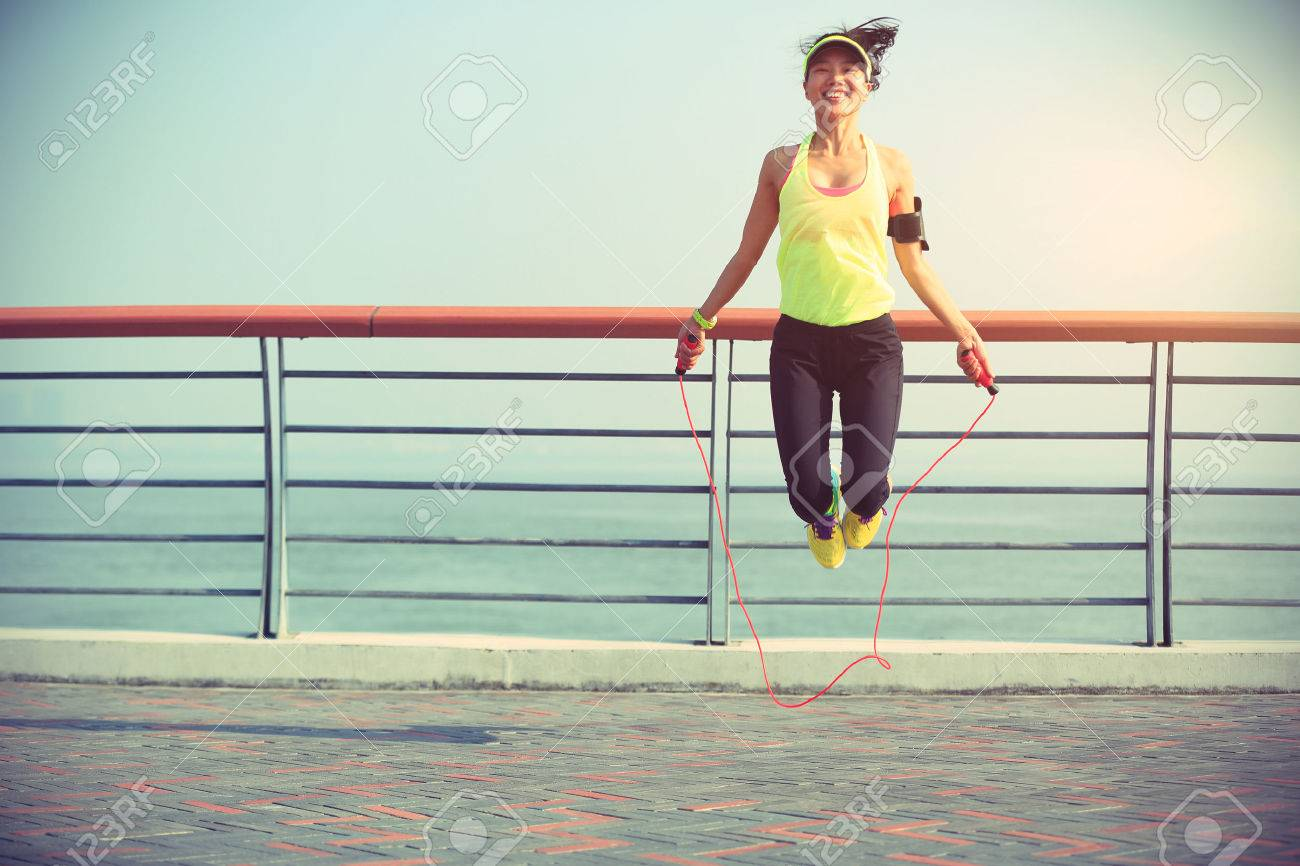 young fitness woman jumping rope at seaside - 51918285