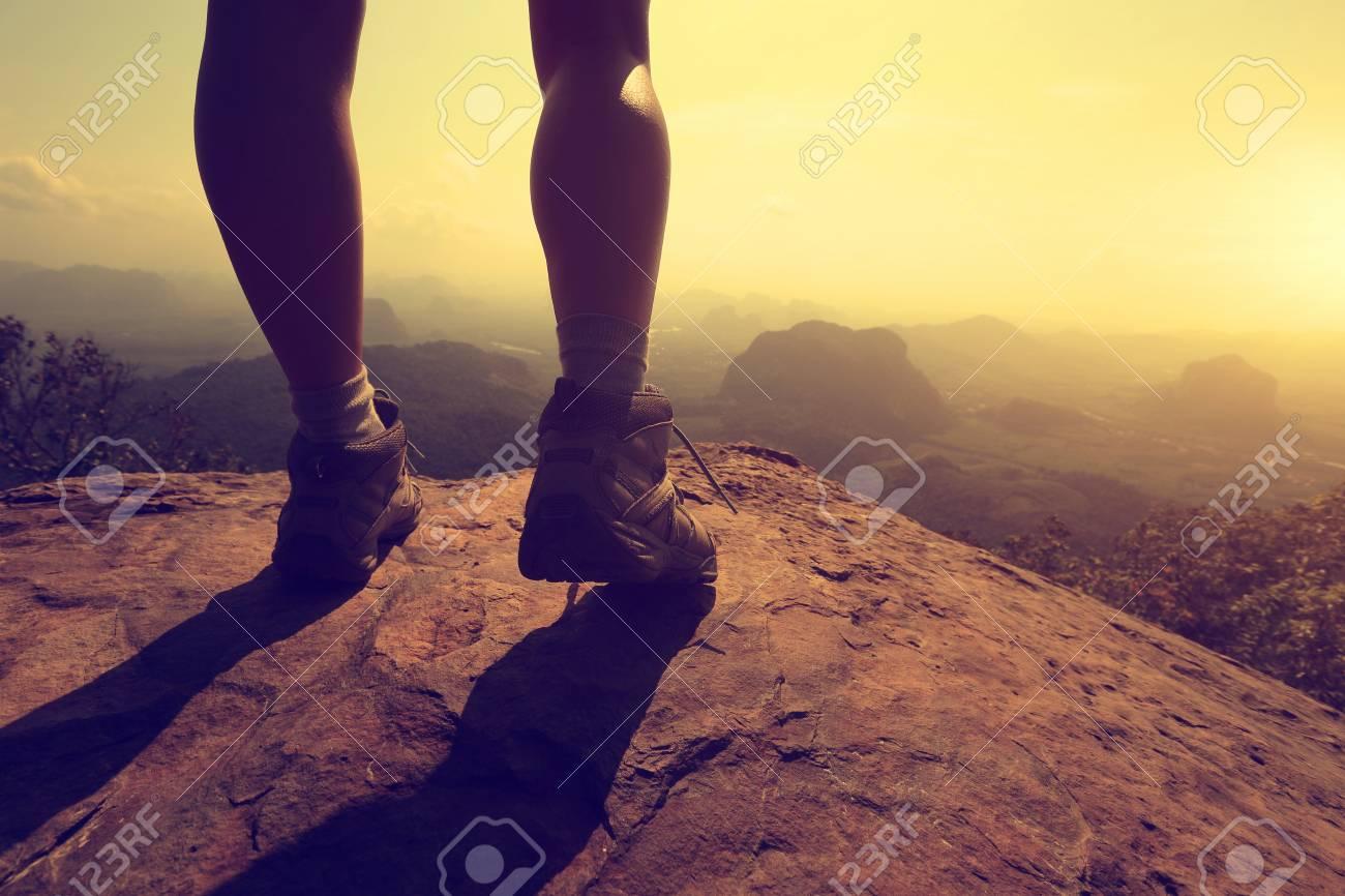 young woman hiker legs on mountain peak rock - 55953117