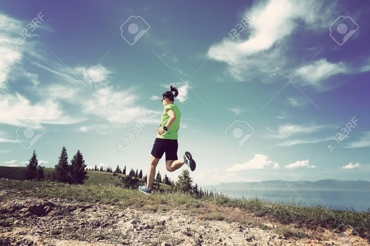 6d2348564d0 Corredor de trail mujer joven sana corriendo en el hermoso pico de la  montaña Foto de