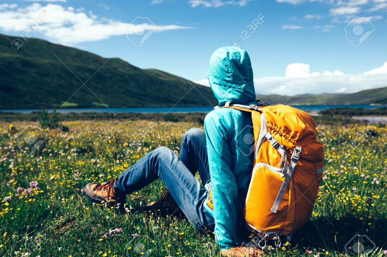 young backpacking woman sit on flowers and grass in high altitude mountains - 91795951