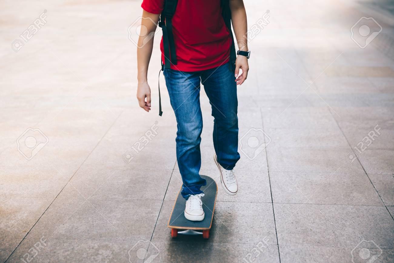 Skateboarder legs riding skateboard on city street - 105522574