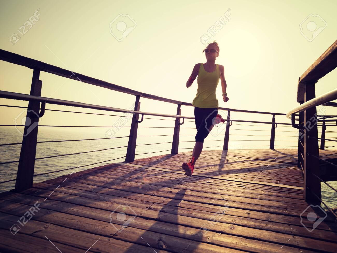 sporty fitness female runner running on seaside boardwalk during sunrise - 120462062
