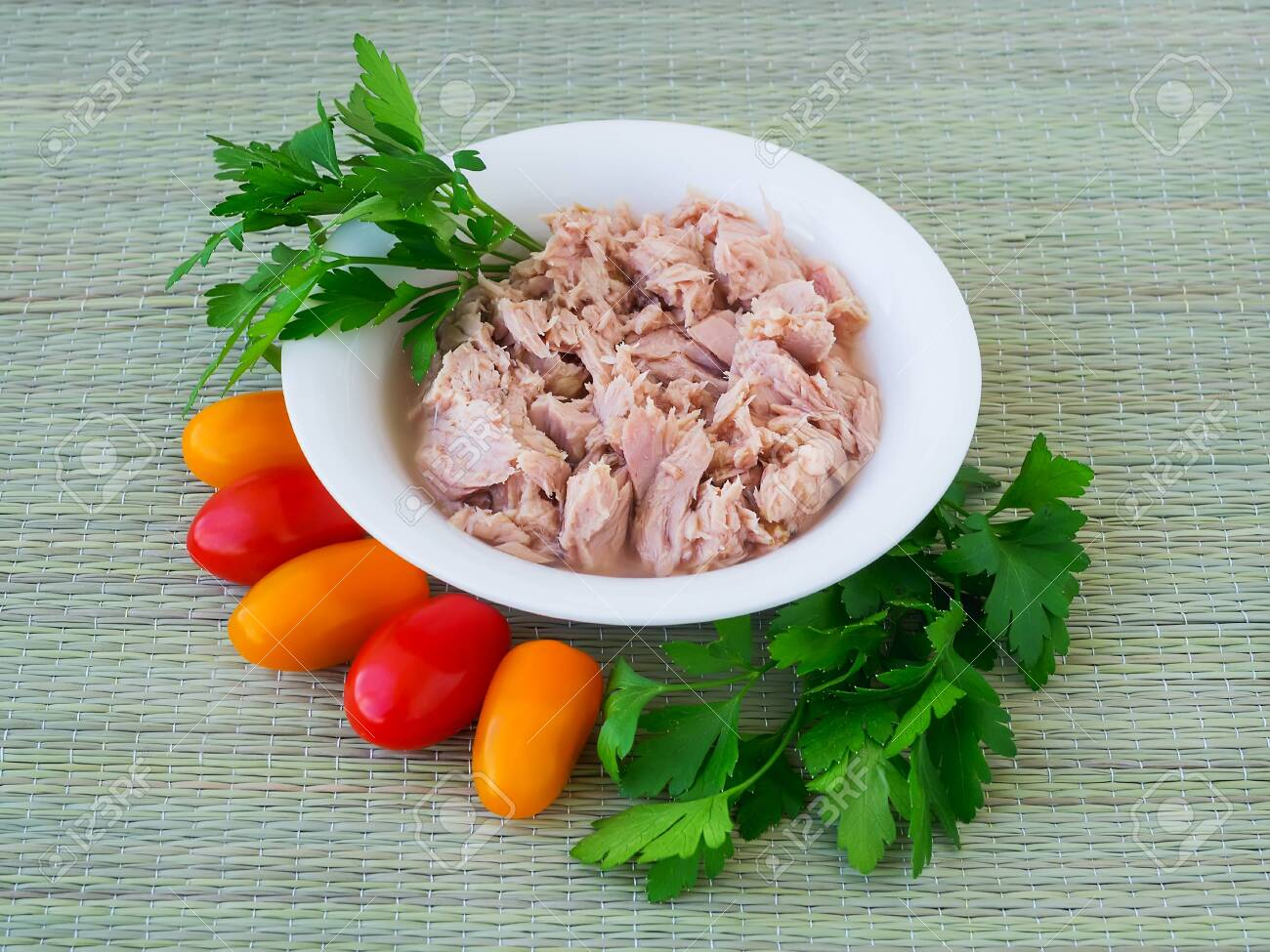 Canned tuna fillet in white porcelain bowl, parsley and some cherry tomatoes on a green table mat made of natural plant fibers. Seafood, healthy eating. Canned tuna for salads. - 124527178