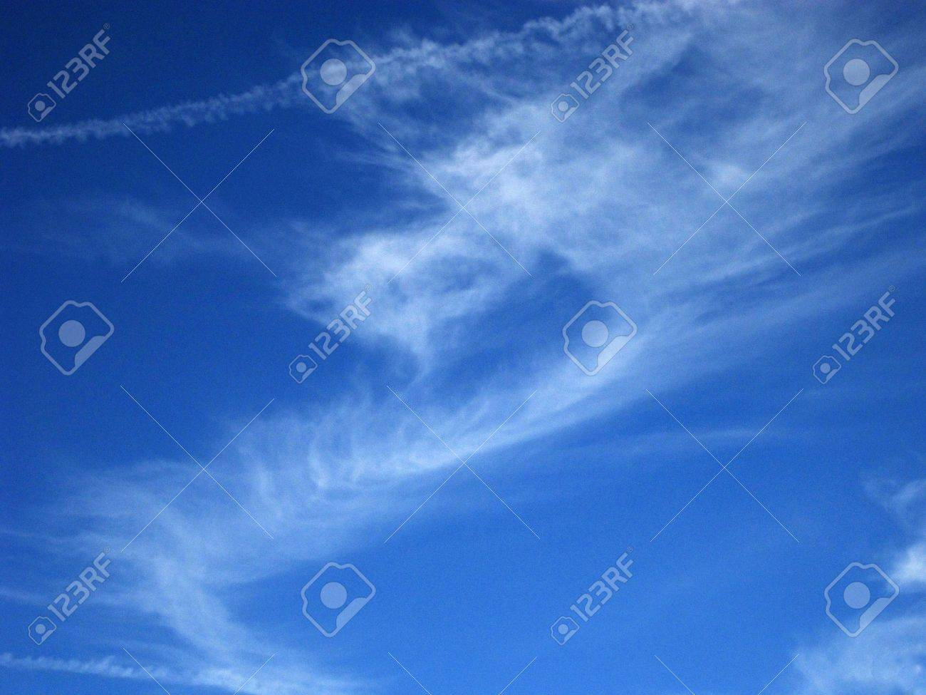 stock photo wispy jet vapor trails mingle with cirrus clouds in a deep blue sky