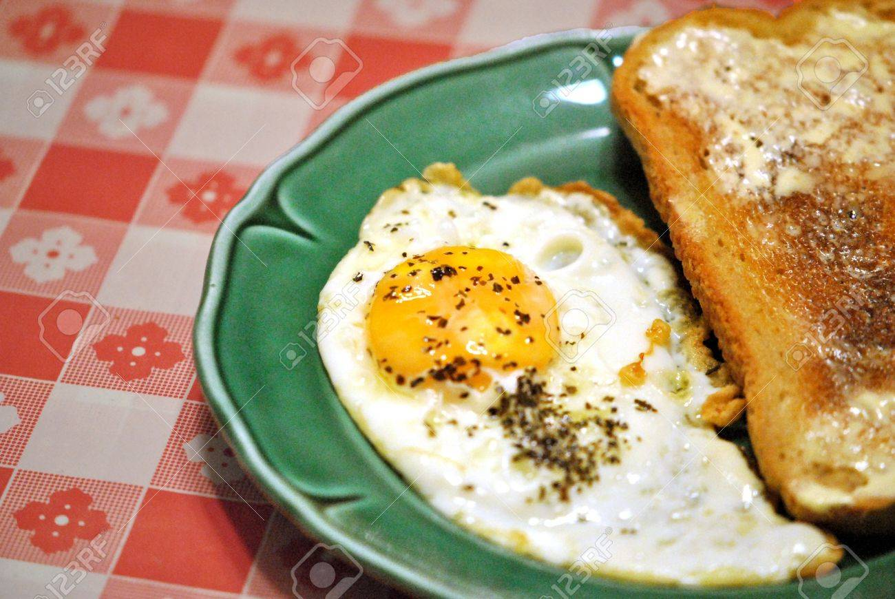 Fried egg, sunny side up, with basil garnish and a slice of hot buttered toast, on a green plate. Stock Photo - 11562193
