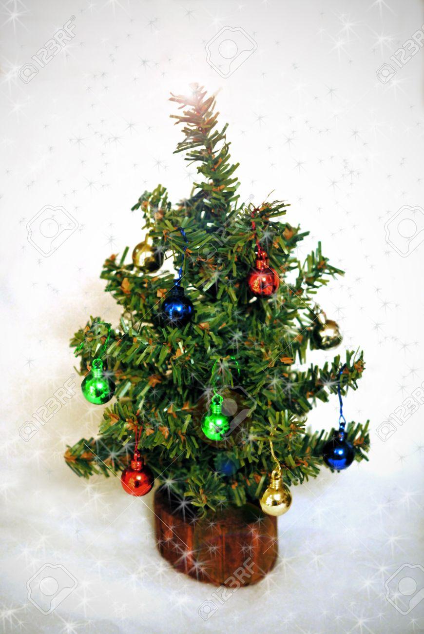 Miniature xmas tree ornaments - Miniature Christmas Tree With Tiny Ornaments Amid Falling Snow Stock Photo 17034475