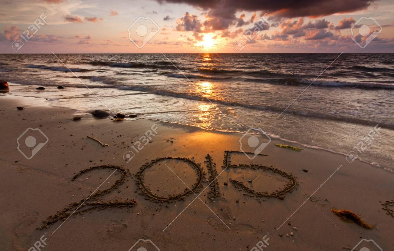Year 2015 written on sand at sunset - 29204739