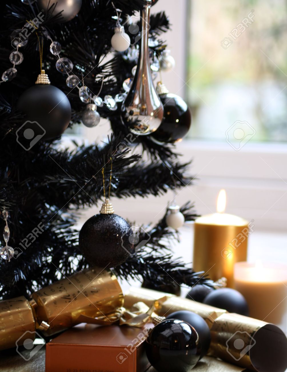 Black Christmas Tree With Silver And Black Balls And Gold Candles And  Crackers Stock Photo
