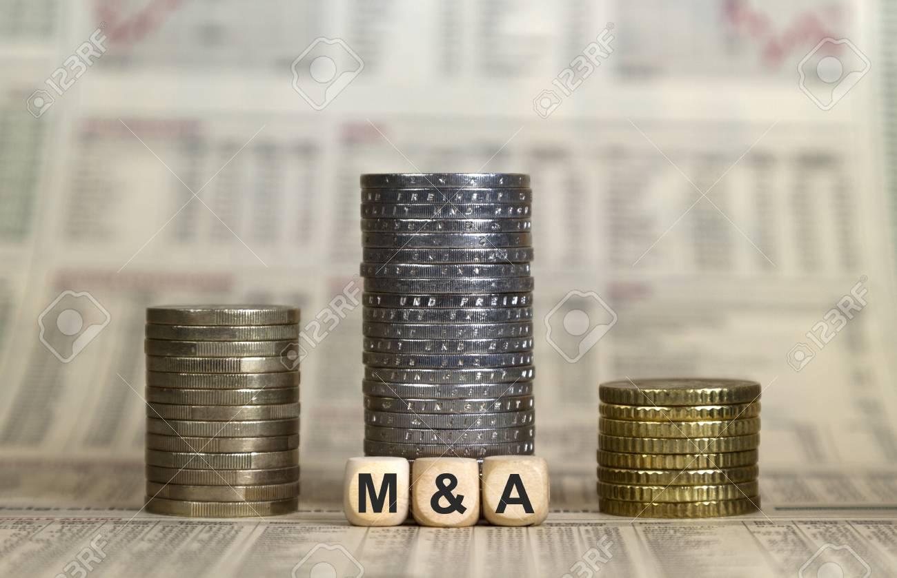 M&A winner's pedestal from coins on a newspaper - 116174960