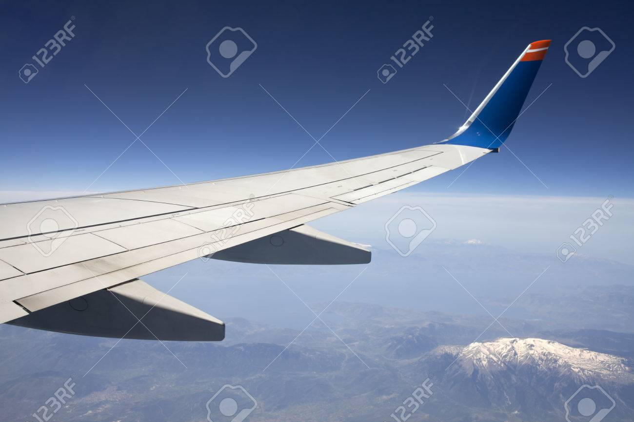 snowy mountains below view from window of a jet plane wing with