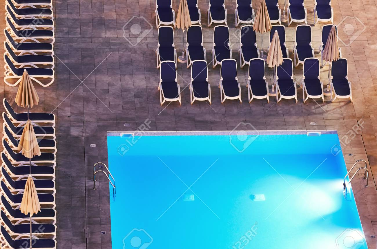 Aerial view of a swimming pool and deck chairs at night.