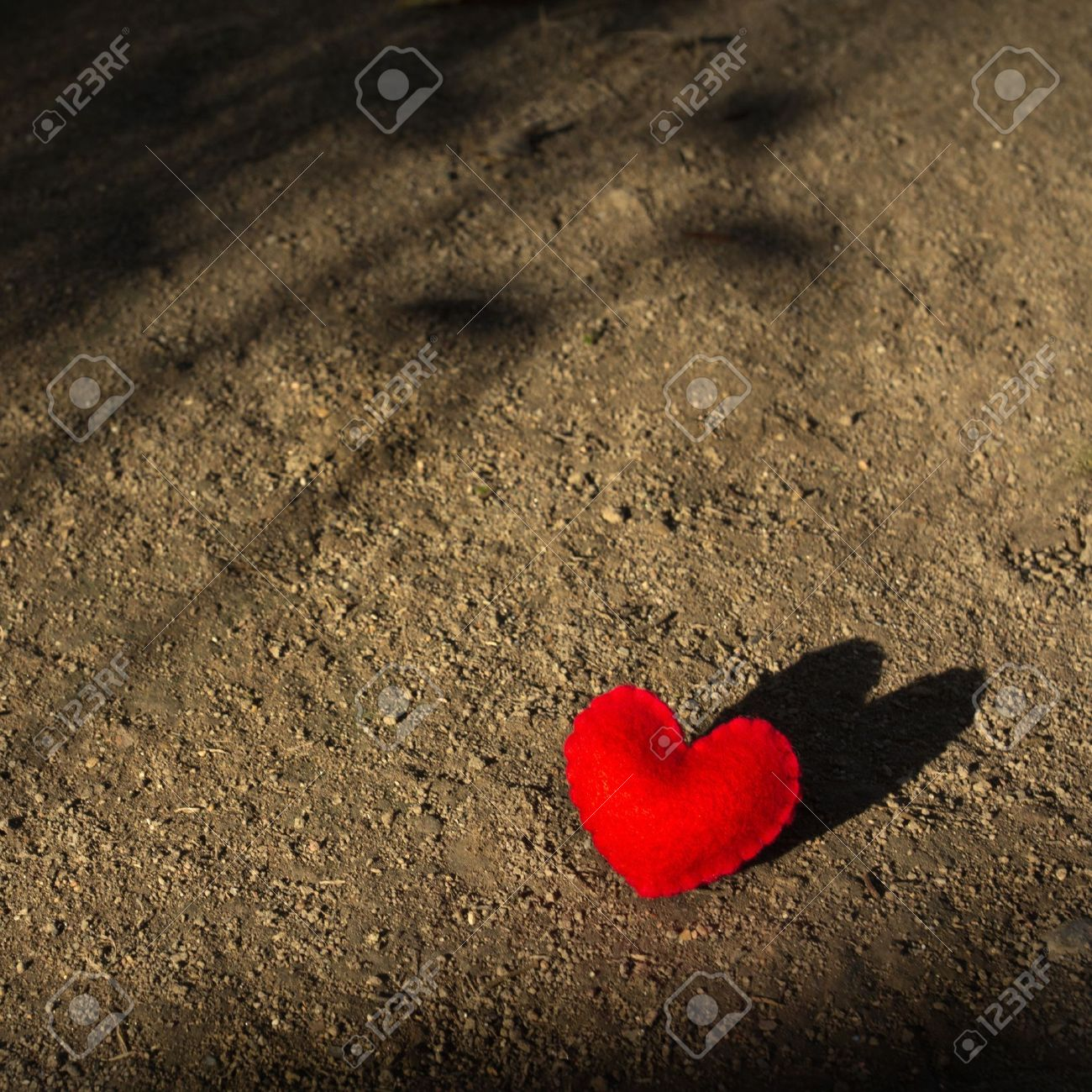 Red Heart Lying Alone On The Ground With Shadow Waiting For Love