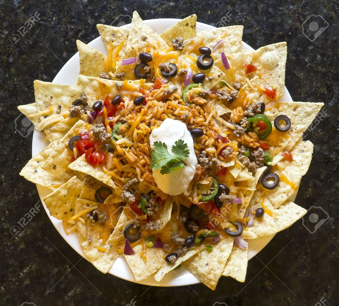 Mexican nachos with sour cream, black olives, ground beef, black beans, tomatoes, shredded cheese, jalapenos, rice, and cilantro Stock Photo - 32147732