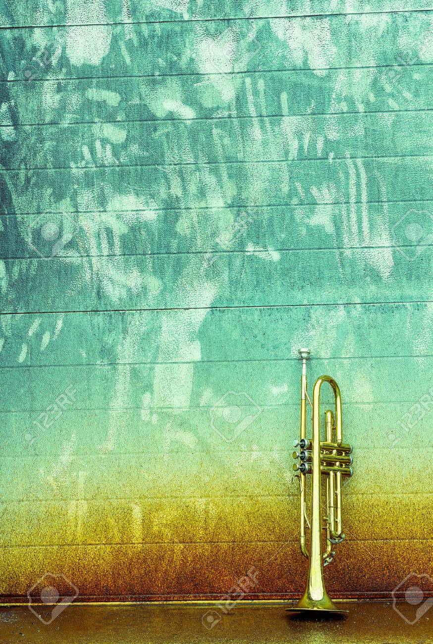 Old worn trumpet stands alone against a grungy wall outside a jazz club Stock Photo - 38171132