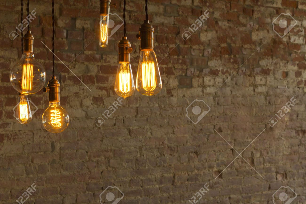 Plain wood table with hipster brick wall background stock photo - Decorative Antique Edison Style Light Bulbs Against Brick Wall Background