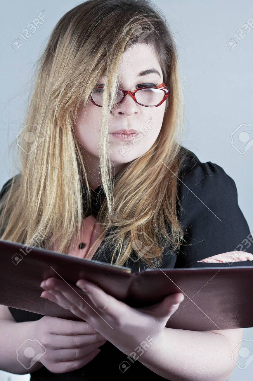 cute nerdy girl with reading glasses posing for a portrait stock