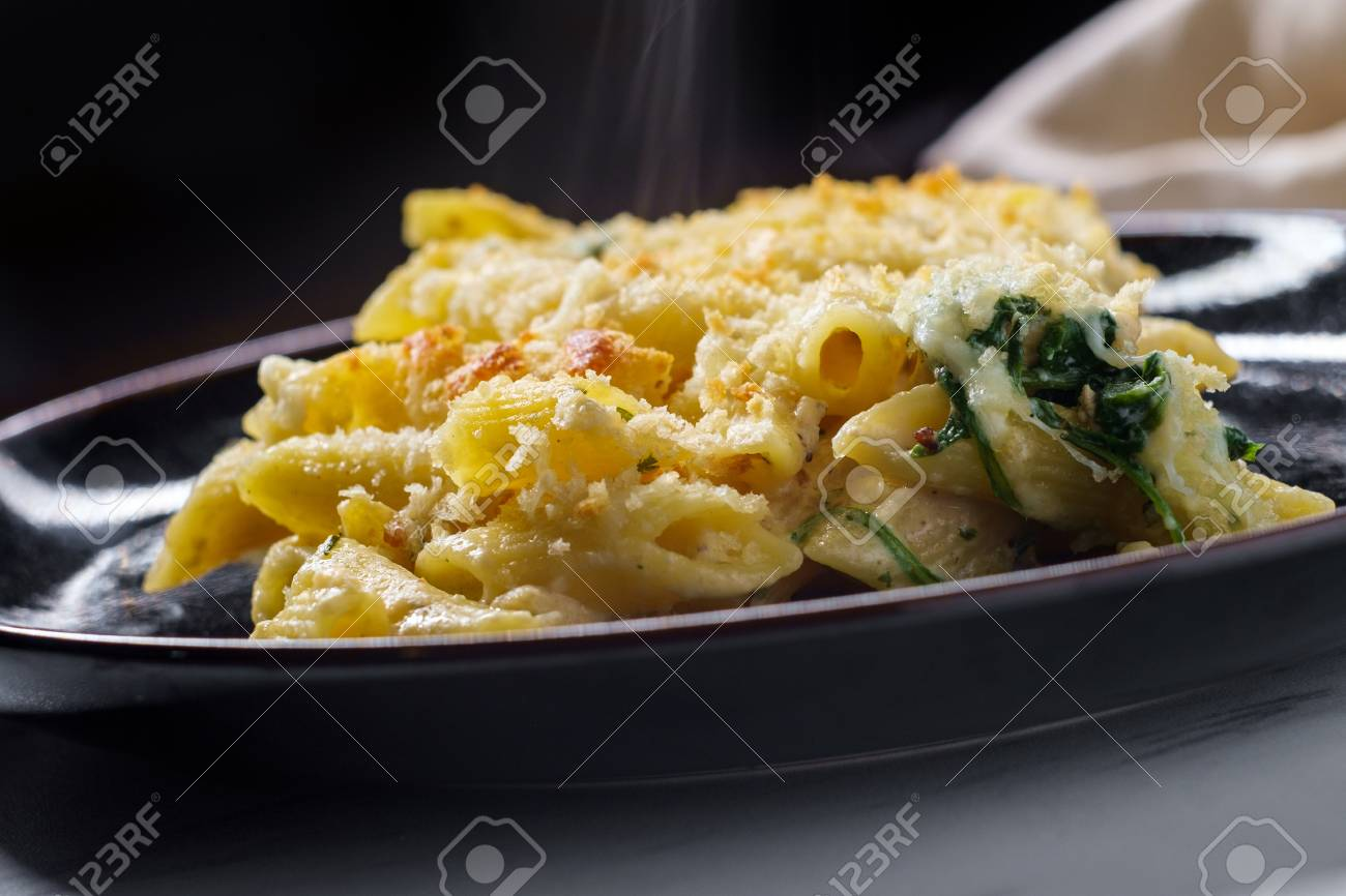 Creamy baked chicken alfredo with penne pasta topped with parmesan and mozzarella cheeses and panko breadcrumbs - 114707927