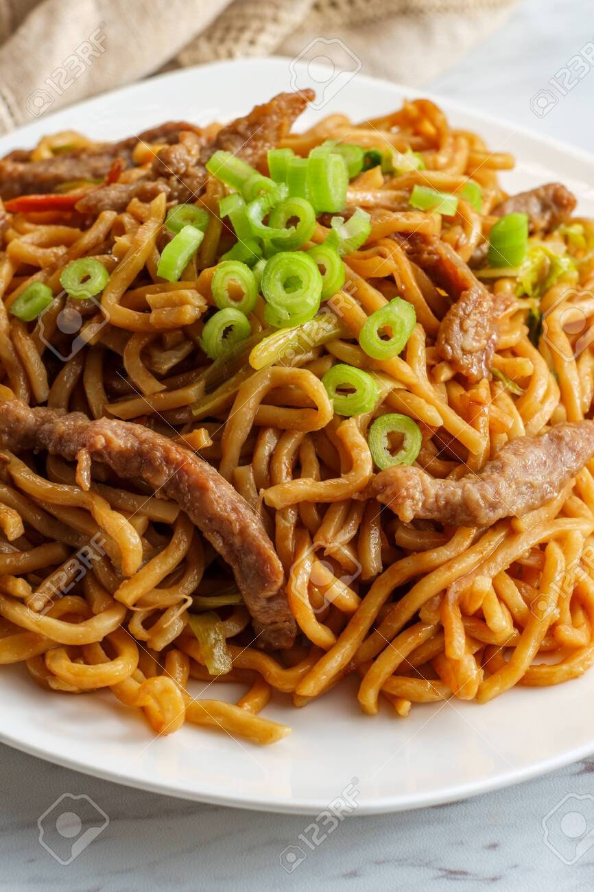 Eating Chinese beef lo mein noodles with chopsticks - 130694007