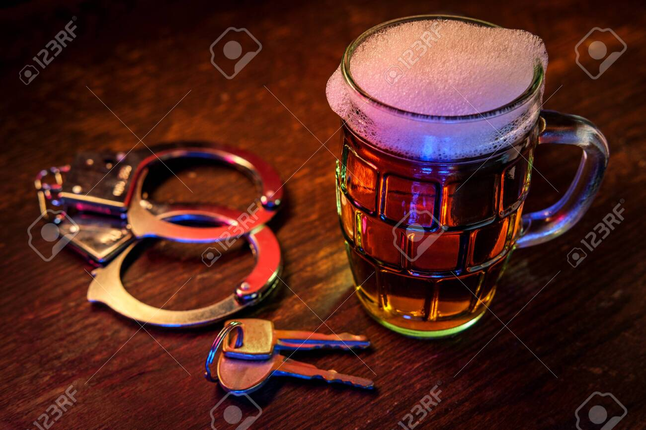 Mug of frothy beer with handcuffs and keys symbolizing drunk driving arrest - 156425105
