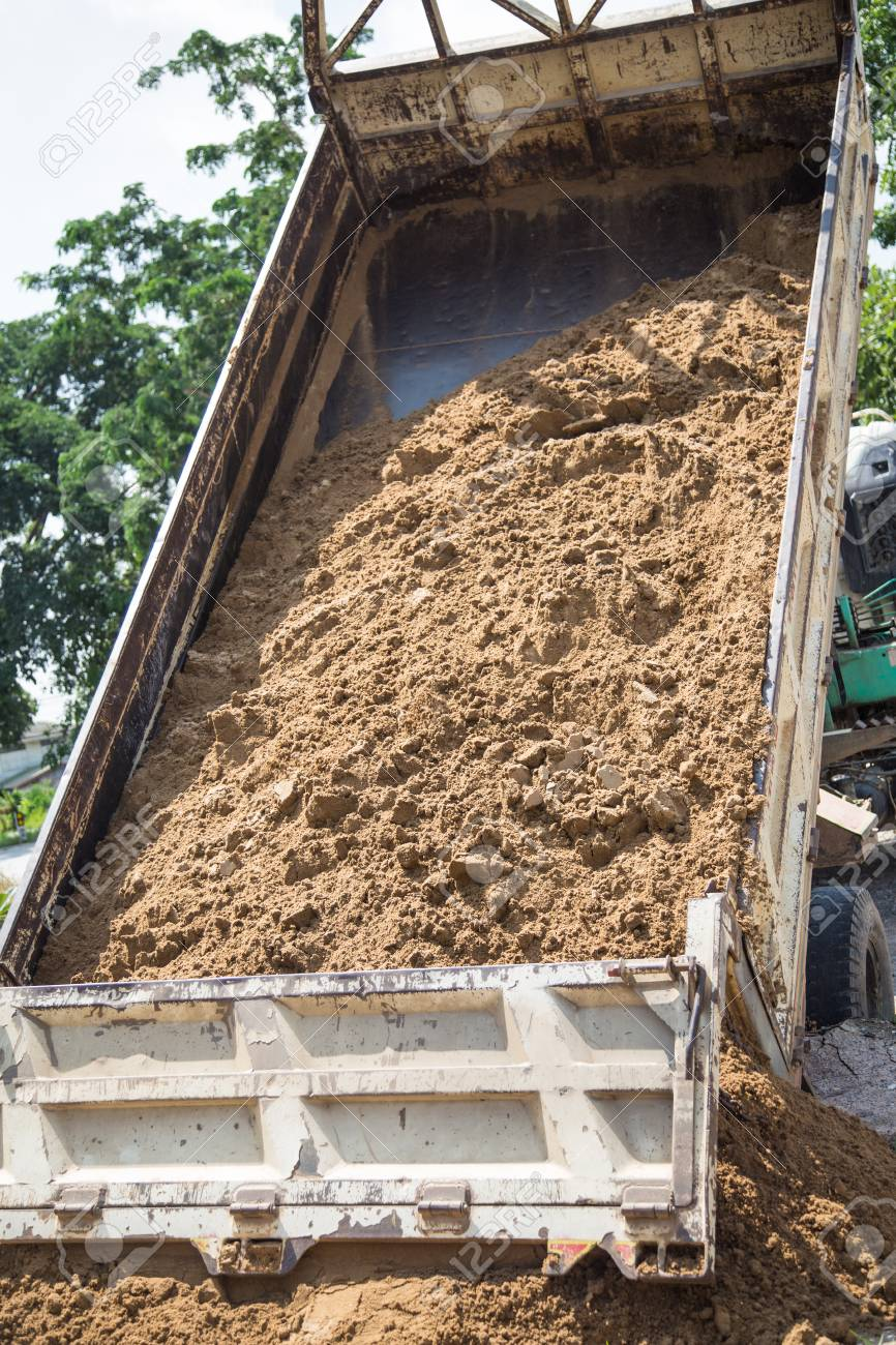 Dump Truck Unloading Sand At Construction Site Stock Photo