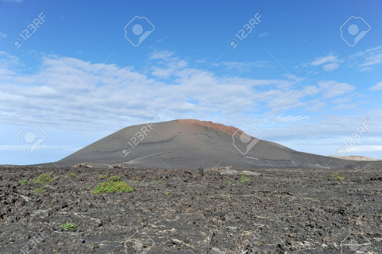 Lanzarote, Canary Islands, Spain  A shallow hill with black sand and small green bushes growing in Timanfaya national park Stock Photo - 27221462