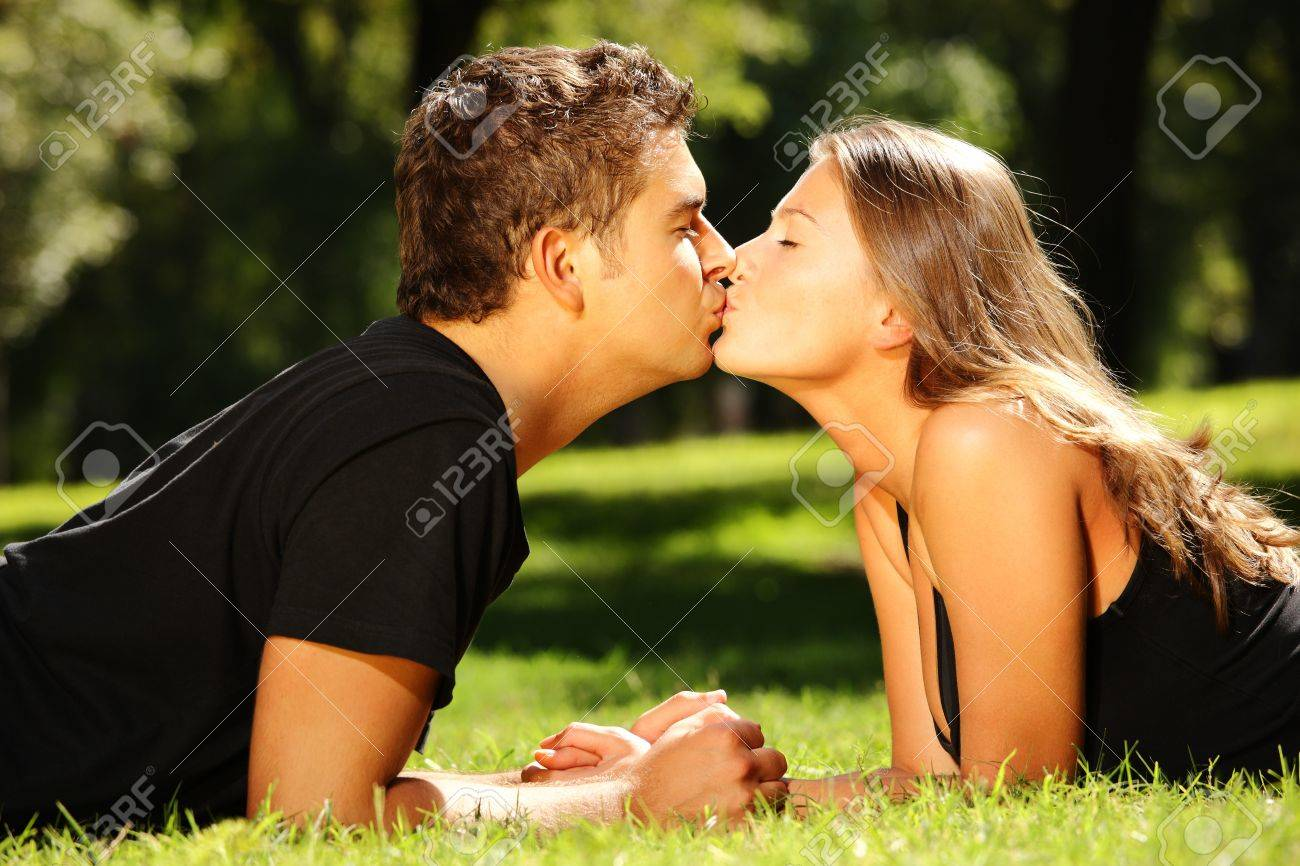 a young cute couple lying on the grass in the park and kissing stock