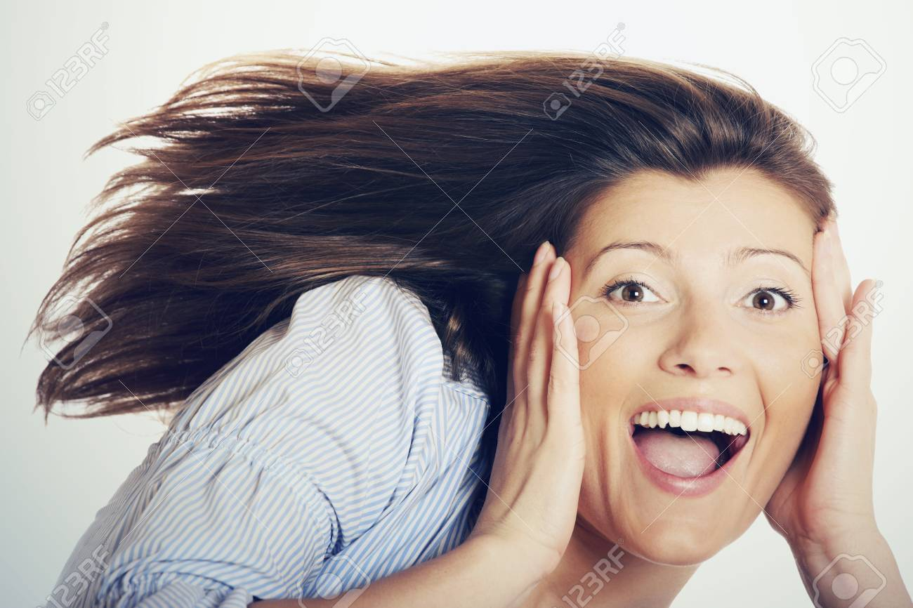 A portrait of a beautiful young surprised woman with long hair holding her head over light background Stock Photo - 9112880