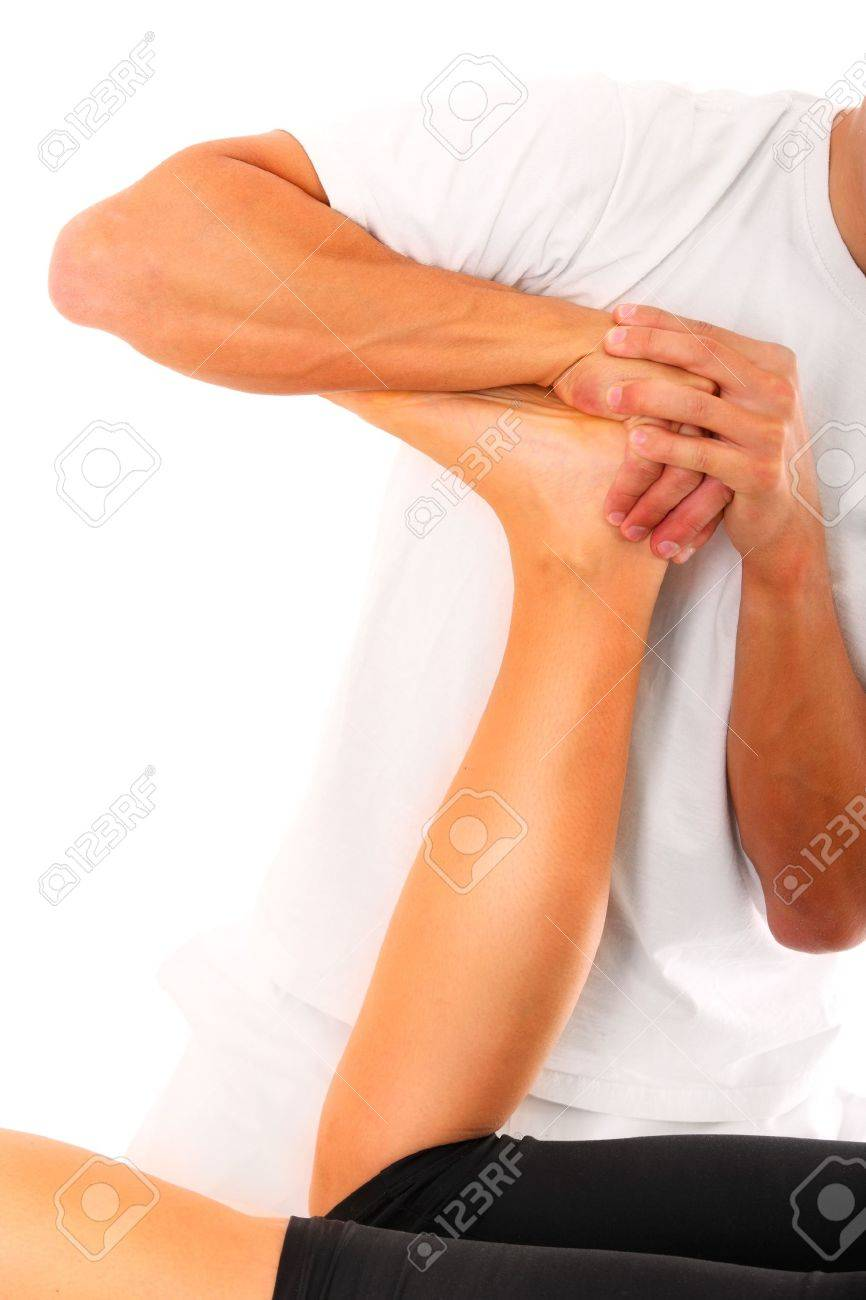 A picture of a physio therapist trying to fix the leg over white background Stock Photo - 12612676