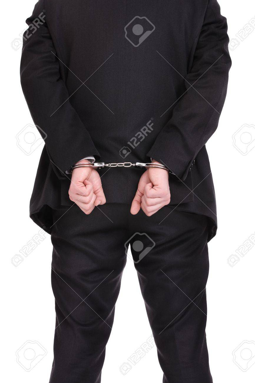 A picture of a businessman in handcuffs standing over white background Stock Photo - 12911282