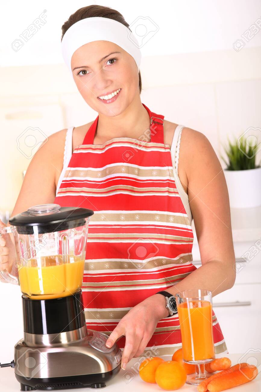 A picture of a young woman preparing fresh fruit juice in the kitchen Stock Photo - 14546587